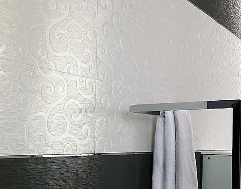 Røff murvegg øverst og fliser i grått og sølv med mønster av
